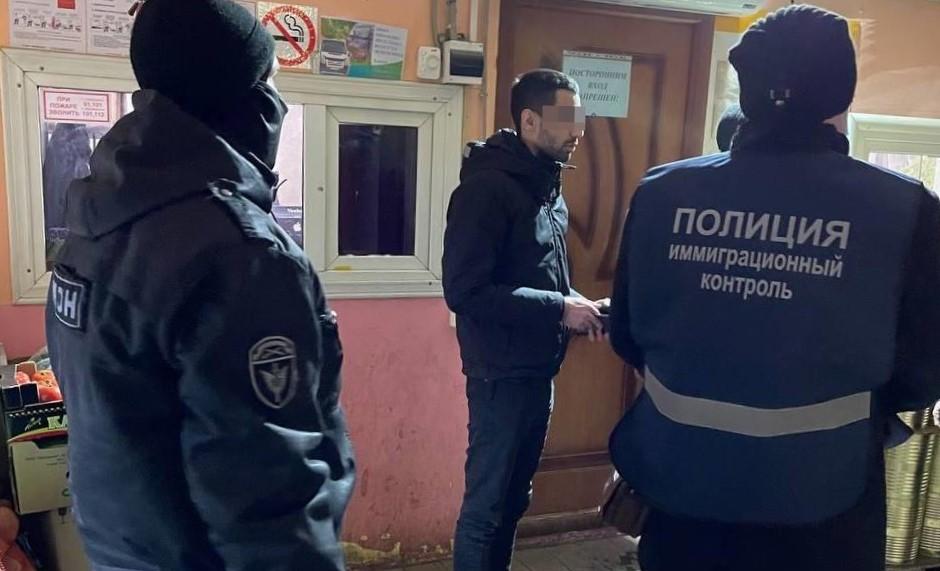 Боец ОМОНа и миграционный полицейский досматривают документы.